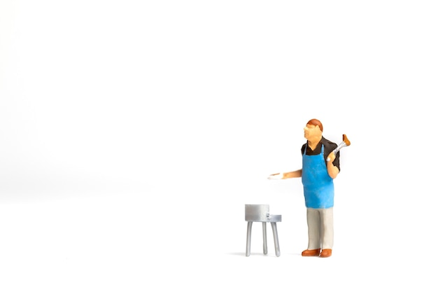 Miniature people ,chef cooking steak on barbecue grill  isolated on white background