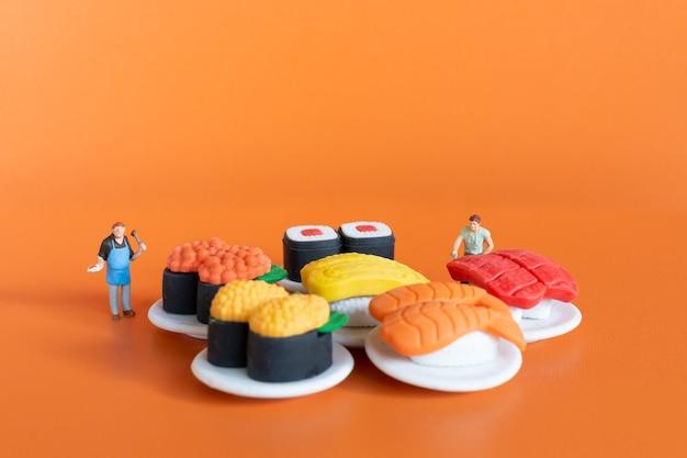 미니어처 사람들, 주황색 배경에 초밥을 만드는 요리사