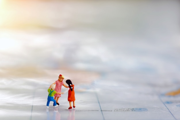 Miniature people: children play by holding hands on world map.