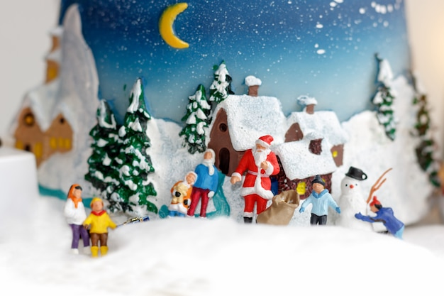 Miniature people: children playing fun with snowman.