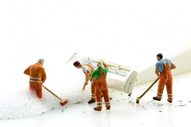Miniature people cleaning dirty white shaver on white background.