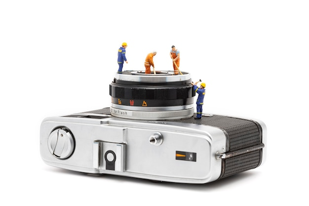 Miniature people cleaning old camera lenses on white background.