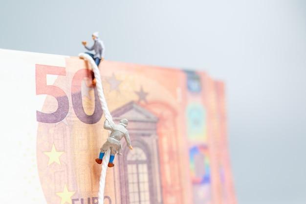 미니어처 사람들, 산악인 유로 지폐 비즈니스 개념에 올라.
