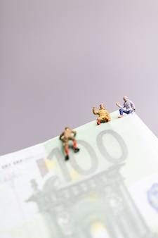 Миниатюрные люди, альпинист поднимается на бизнес-концепцию банкноты евро.