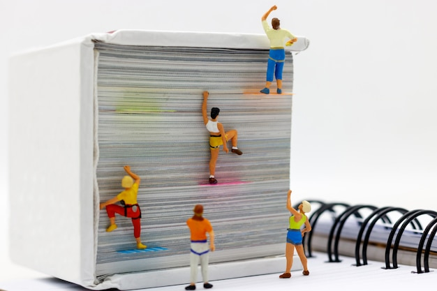 Miniature people climbing book with challenging route on cliff.