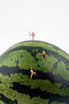 Miniature people climbing watermelon
