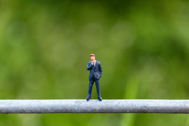 Miniature people concept with businessman stand on a wire