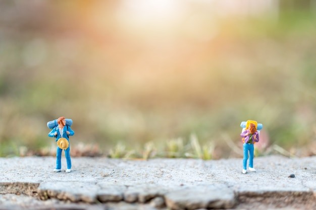 Miniature people concept with travelers miniature with backpack standing on the road