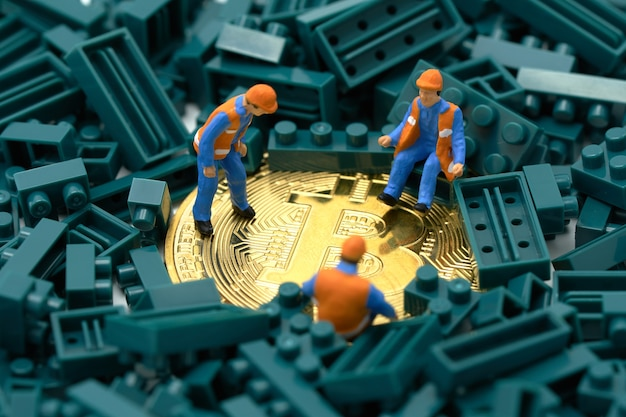Miniature people construction worker digs a gold bit coin