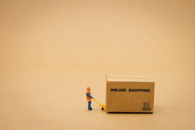 Miniature people construction worker online shopping with a shopping cart