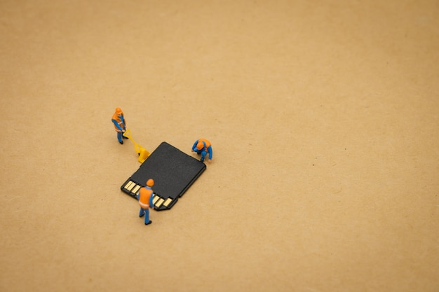 Miniature people construction worker repair with storage card or memory card