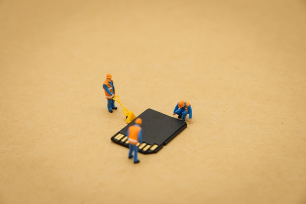 스토리지 카드 또는 메모리 카드로 소형 사람들 건설 노동자 수리