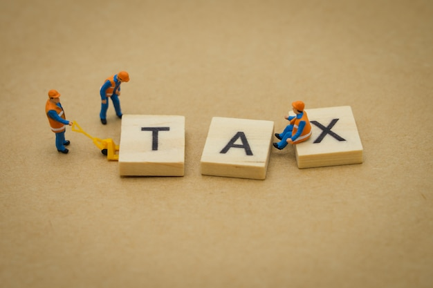 Miniature people construction worker standing with wood word tax u