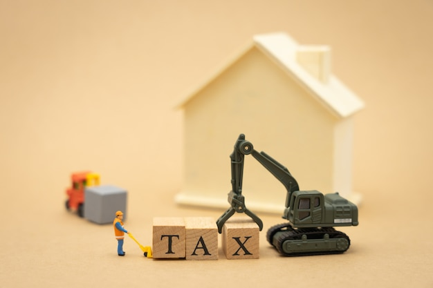 Miniature people construction worker standing with wood word tax