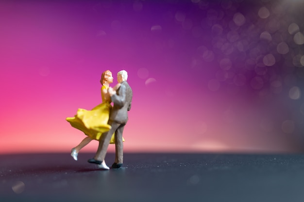 Miniature people, couple dancing with colorful  background