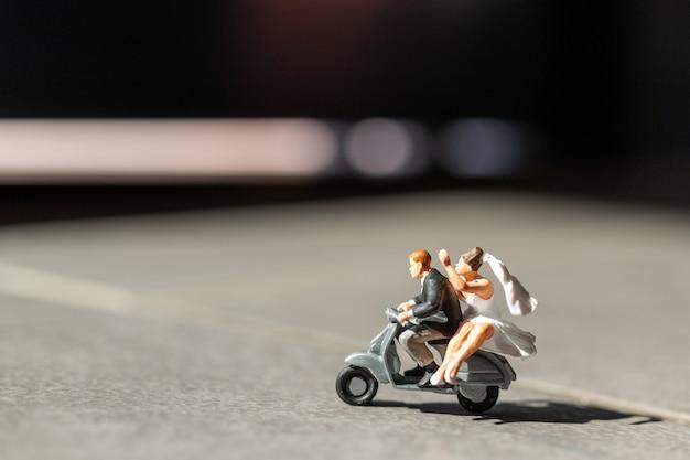 Миниатюрные люди, влюбленная пара катается на мотоцикле