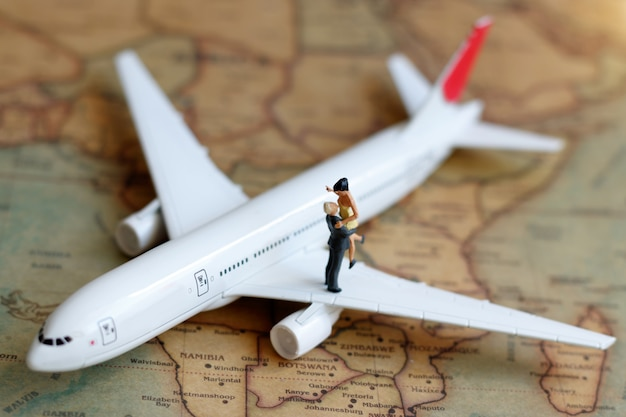 Miniature people couple lover standing on airplane.