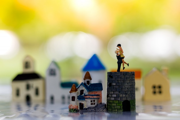 Miniature people couple lover standing on castle and tiny house.