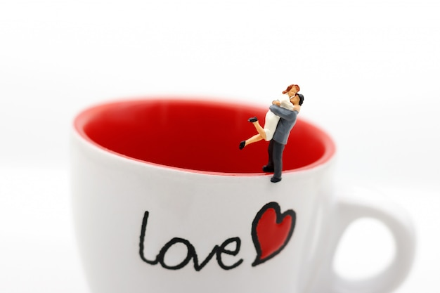 Miniature people couple lover standing on cup off coffee, lovely concept.