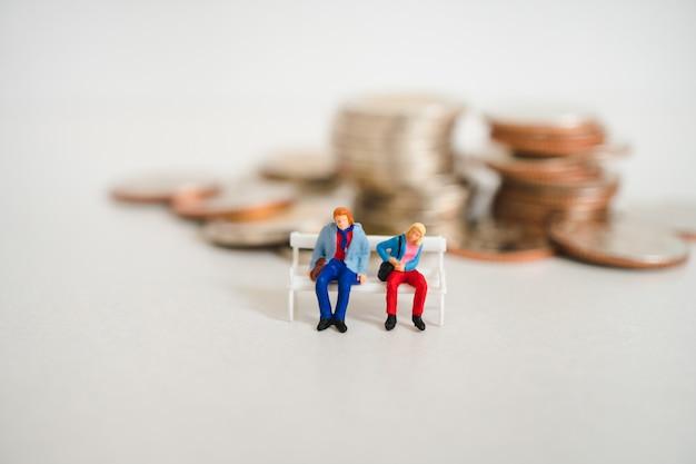 Миниатюрные люди, пара мужчина и женщина, сидя на фоне стека монет