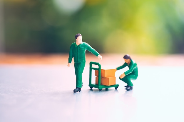 Miniature people, couple man carrying box using for logistic and business concept