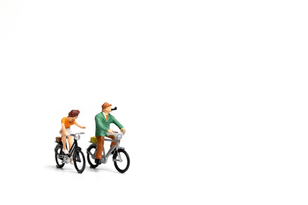 Miniature people: couple ride bicycle on white background