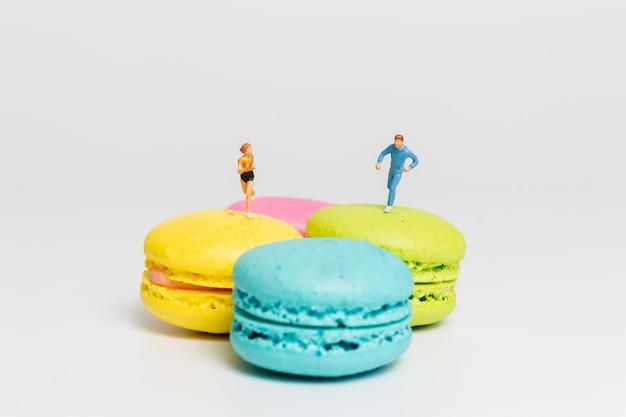 미니어처 사람들, 다채로운 프랑스 마카롱에서 달리는 커플,