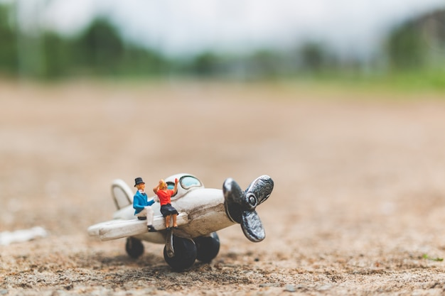 Miniature people: couple sitting on the airplane