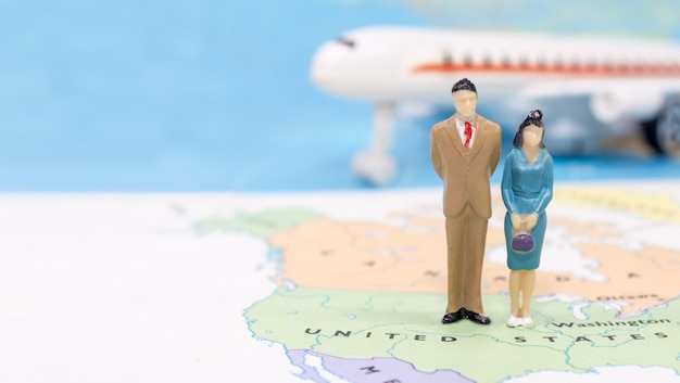 Miniature people, couple standing on map american