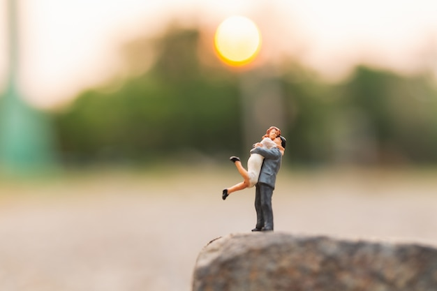 Miniature people : couple standing on the rock cliff