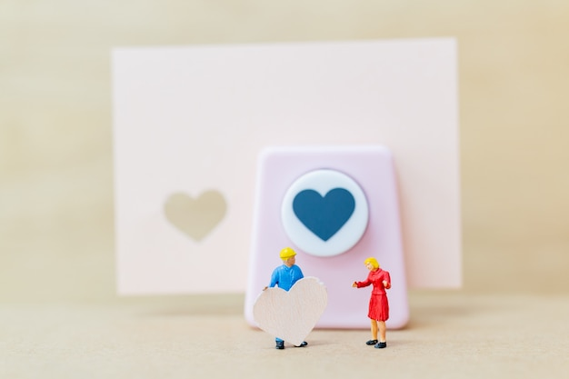 Miniature people : couple with  paper heart on wooden  background