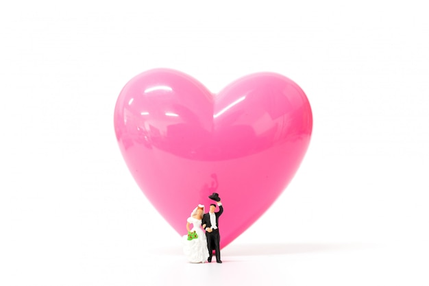 Miniature people  couple with  pink heart on white  background