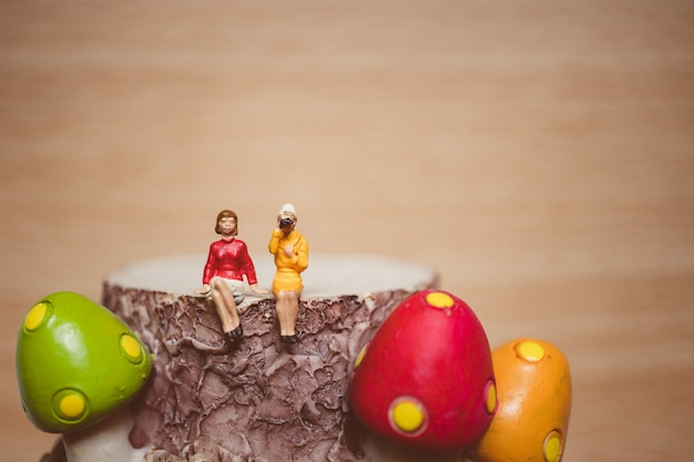 Miniature people, couple woman sitting on mushroom timber using for relaxation concept - vintage fil