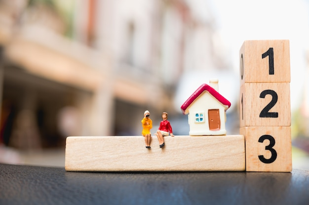 Miniature people, couple woman sitting on wooden block number with mini house using as business, pro