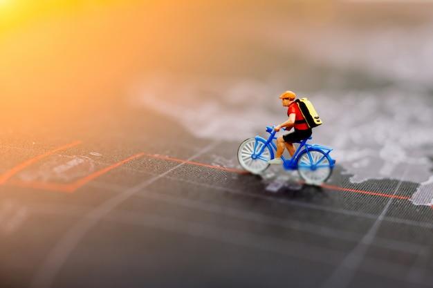 世界地図上でサイクリングするミニチュアの人々。旅行、スポーツ、ビジネスコンセプト。