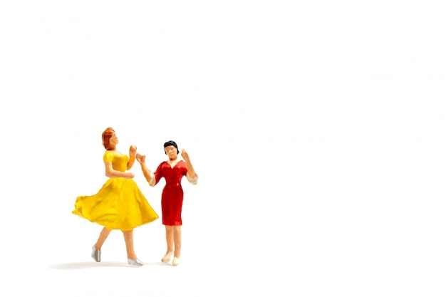 Miniature people dancing on white