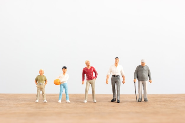 Miniature people in different ages stand on wood floor with white background