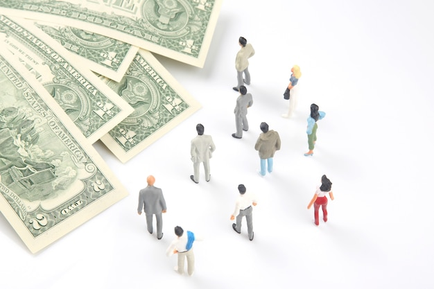Miniature people. different businessman stands near dollar money. investments and earnings for work
