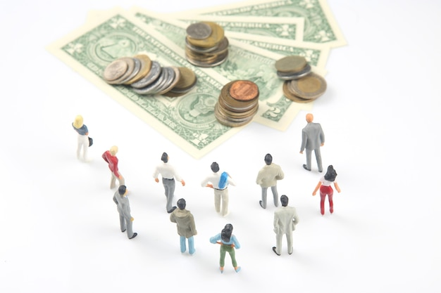Miniature people. different people are standing near dollar money. investments and earnings for work