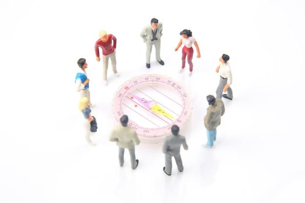 Миниатюрные люди. у компаса стоят разные люди. поиск направления в жизни