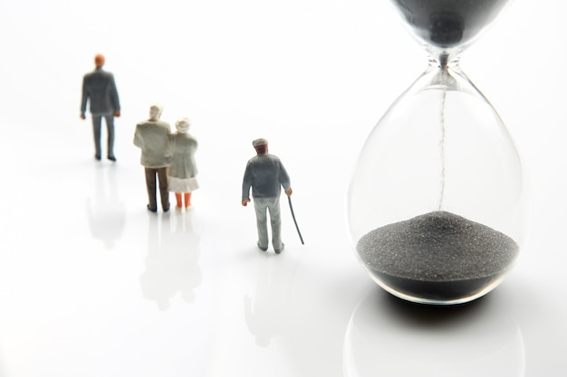 Miniature people. different people are walking next to the hourglass. lifespan of humanity