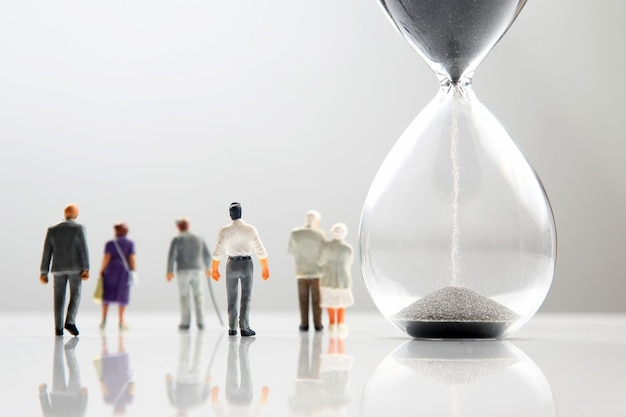 Miniature people. different people are walking next to the hourglass. lifespan of humanity Premium Photo