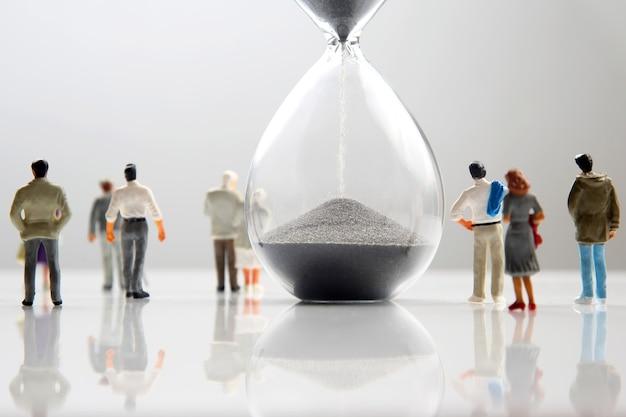 ミニチュアの人々。砂時計の横をさまざまな人が歩いています。人類の寿命