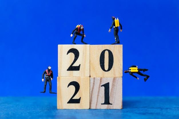 Miniature people divers diving around wooden block 2021, happy new year concept