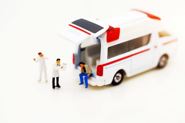 Miniature people: doctor and patient standing with ambulance.