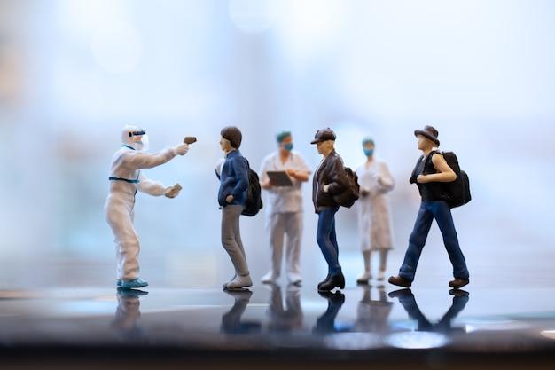 미니어처 사람들 코로나 바이러스와 독감 발발 동안 안면 마스크를 착용하는 의사.