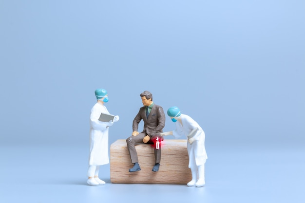 Miniature people doctors treat rheumatism, osteoarthritis , world arthritis day concept