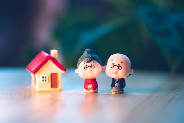 직장 퇴직 및 보험 개념으로 사용하는 미니 하우스와 함께 서 있는 미니어처 사람, 노인 남성 및 여성