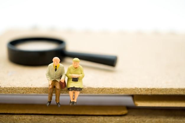 ミニチュアの人々、仕事の退職とhとして使用している虫眼鏡で本に座っている高齢者