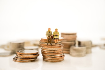 Miniature people, elderly people sitting on stack coins using as job retirement